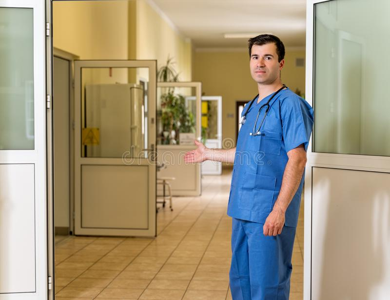Middle age male doctor inviting patients in to the clinic or hospital stock photos