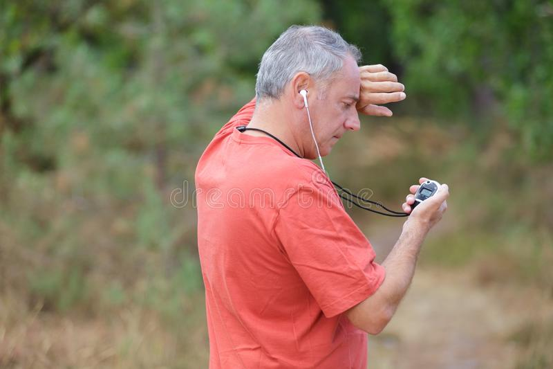 Middle-age male jogger taking break from running workout stock image