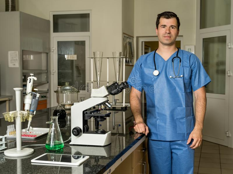Middle age male laboratory technician standing next to compound microscope royalty free stock image