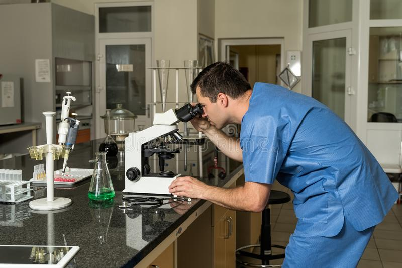Middle age male laboratory technician working on compound microscope, laboratory equipment and glassware in background royalty free stock photos