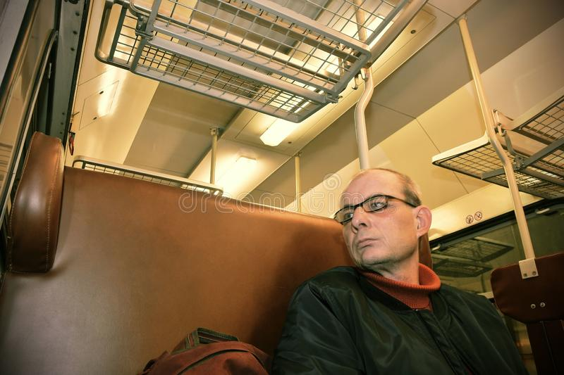 Middle age man looking out of the window of train. Passenger during travel by high speed express train in Europe stock photos