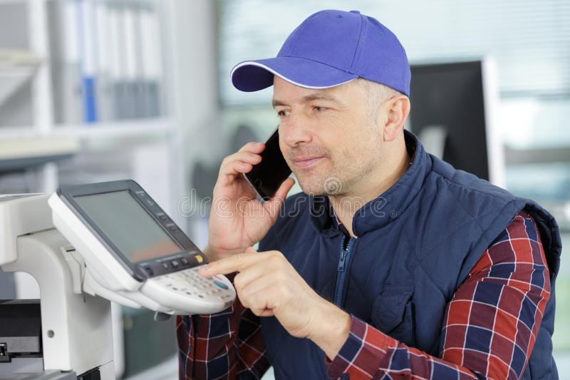 Middle age man on phone fixing printer stock photography