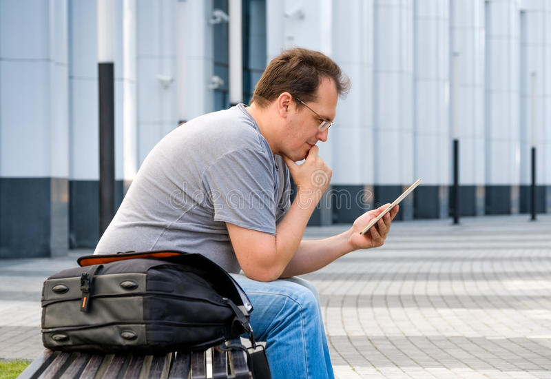 Middle age man reading tablet. Sitting outdoors stock image
