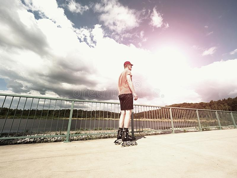 Middle age man in red t-shirt with inline skates ride in summer park, popular outdoor skating. Middle age man in red t-shirt with inline skates ride in summer stock photo