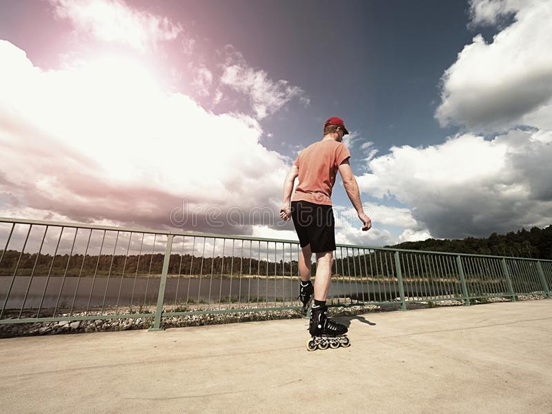 Middle age man in red t-shirt with inline skates ride in summer park, popular outdoor skating. Middle age man in red t-shirt with inline skates ride in summer stock images