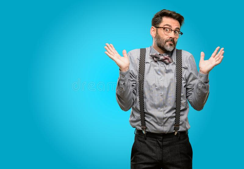 Middle age man wearing a suit. Middle age man, with beard and bow tie doubt expression, confuse and wonder concept, uncertain future shrugging shoulders stock photo