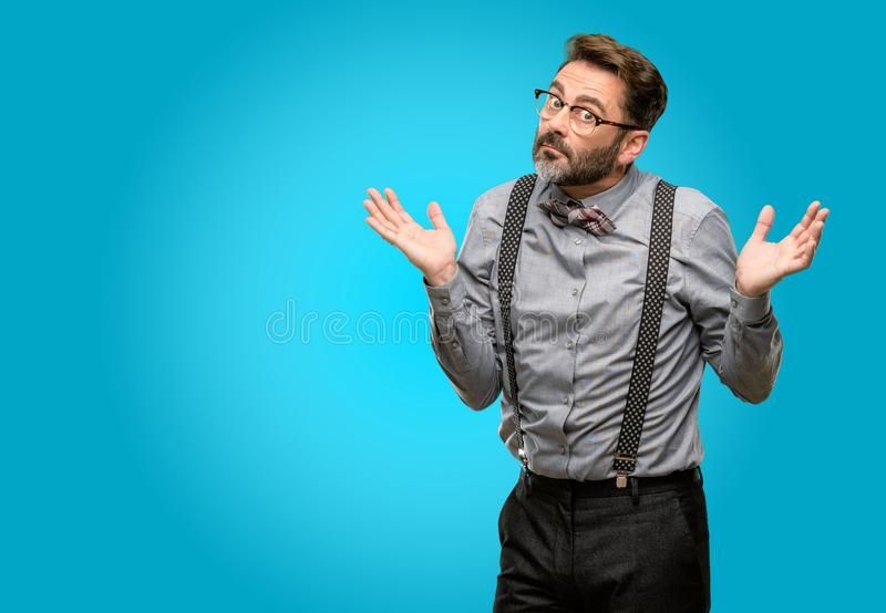 Middle age man wearing a suit. Middle age man, with beard and bow tie doubt expression, confuse and wonder concept, uncertain future shrugging shoulders stock photos
