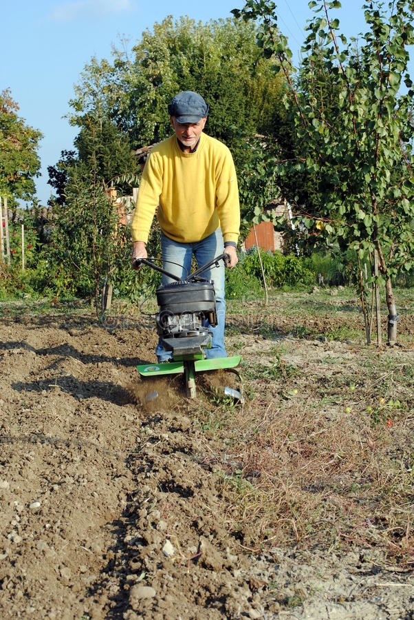 Free Middle Age Man With A Rototiller Stock Photography - 23404982