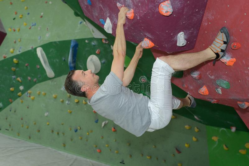 Middle-age man climber on artificial climbing wall stock images