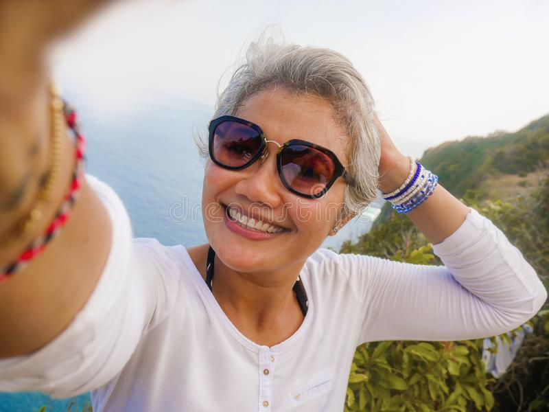 Middle age 50s happy and cheerful Asian woman with grey hair taking selfie with mobile phone at beautiful tropical beach island stock images