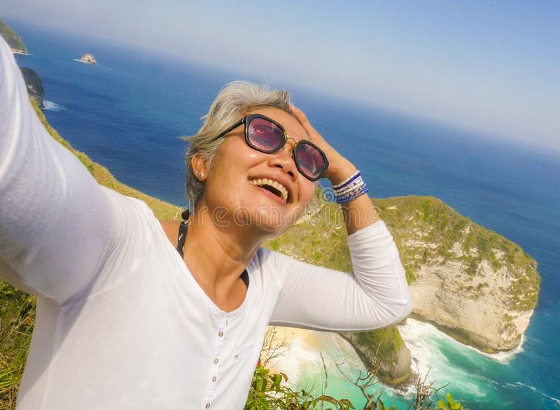 Middle age 50s happy and cheerful Asian woman with grey hair taking selfie with mobile phone at beautiful tropical beach island stock photos