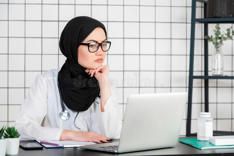 Middle age senior arab nurse woman wearing hijab at medical office with hand on chin thinking about question, pensive stock photos