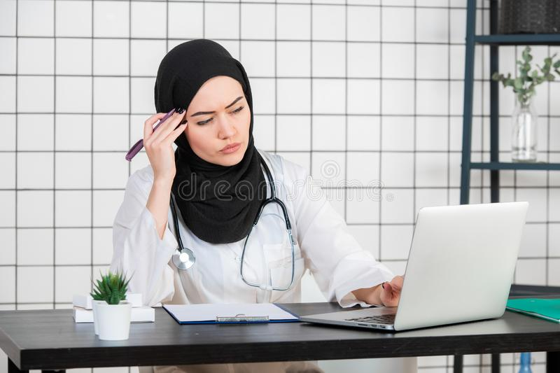 Middle age senior arab nurse woman wearing hijab at medical office with hand on chin thinking about question, pensive stock image