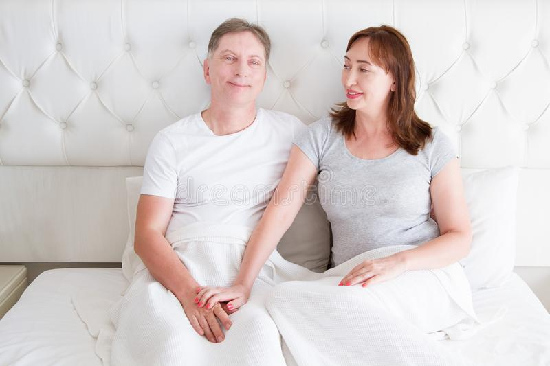 Middle age senior couple in bed. Template and blank t shirt. Front view. Healthy relationships. Copy space. Middle age senior couple in bed. Template and blank stock photo