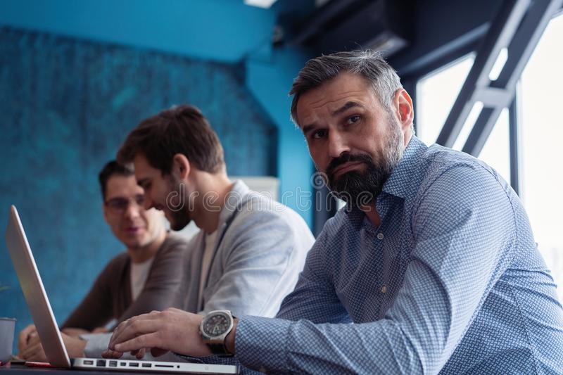 Middle age top manager working at the wood table in modern interior design office. Stylish bearded businessman using stock photography