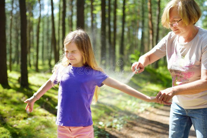 Middle age woman applying insect repellent to her granddaughter before forest hike beautiful summer day. Protecting children from stock photography