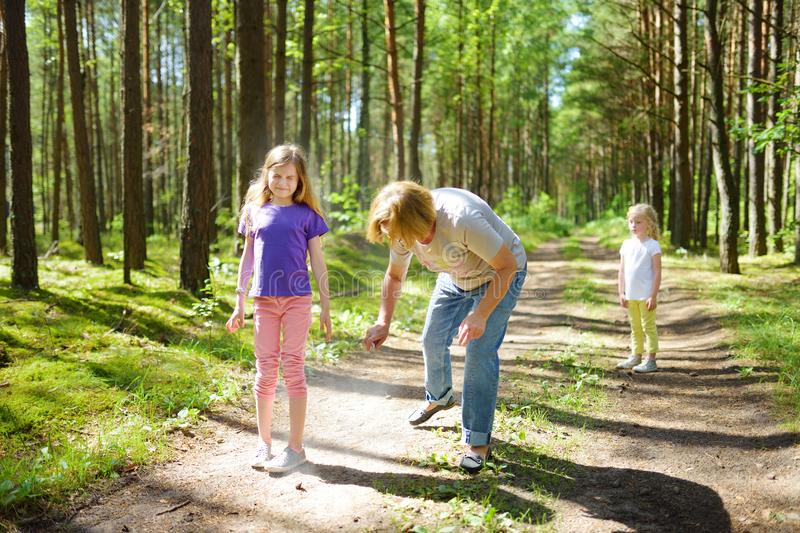 Middle age woman applying insect repellent to her granddaughter before forest hike beautiful summer day. Protecting children from. Middle age women applying stock photo