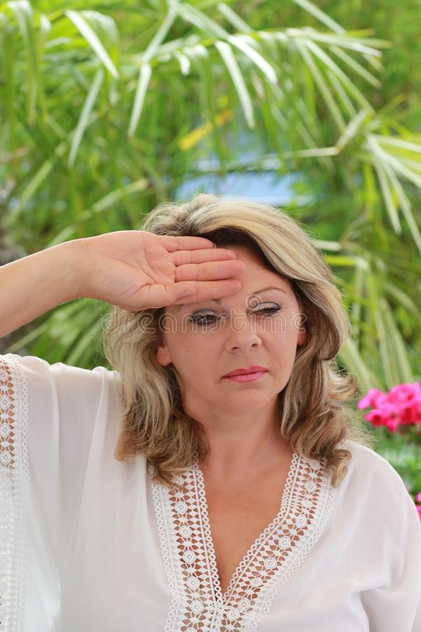 Woman with dizziness in summer. Middle age woman with dizziness hloding her hand at her forehead stock images