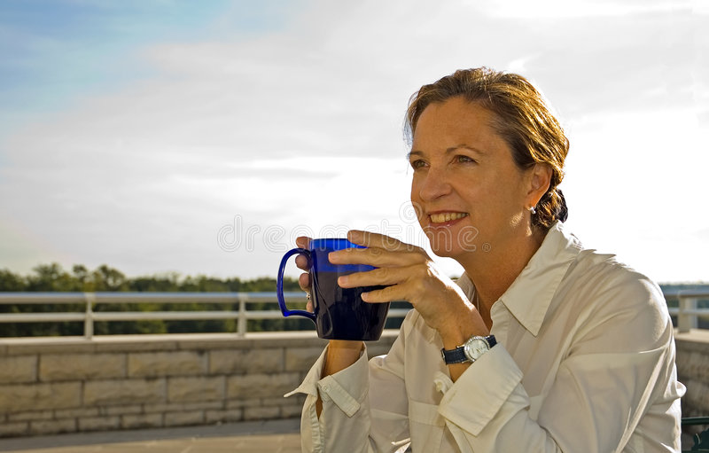 Middle Age Woman Drinking Coffee. Middle aged woman smiling while drinking a fresh cup of coffee on the office patio in the Morning