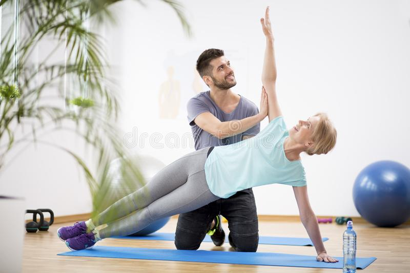 Middle age woman exercising on blue mat during physiotherapy with young male doctor. Middle age women exercising on blue mat during physiotherapy with young royalty free stock photos