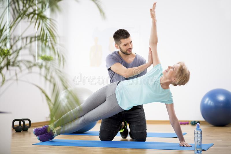 Middle age woman exercising on blue mat during physiotherapy with young male doctor royalty free stock images