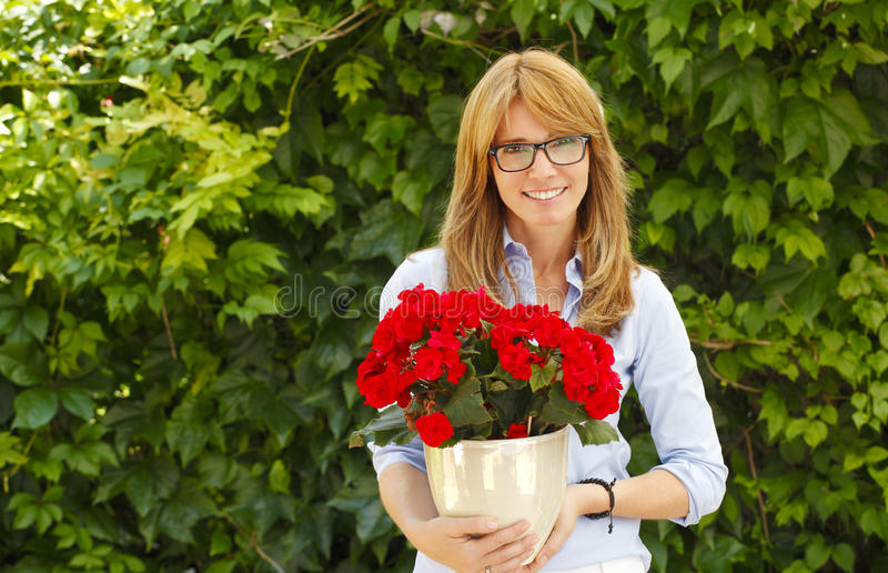 Middle age woman with flower pot. Middle age woman celebrate her birthday royalty free stock photo