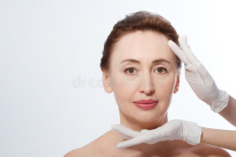 Middle age woman getting spa treatment. Face massage. Anti aging botox and collagen. Plastic surgery concept with doctor hands iso stock photos