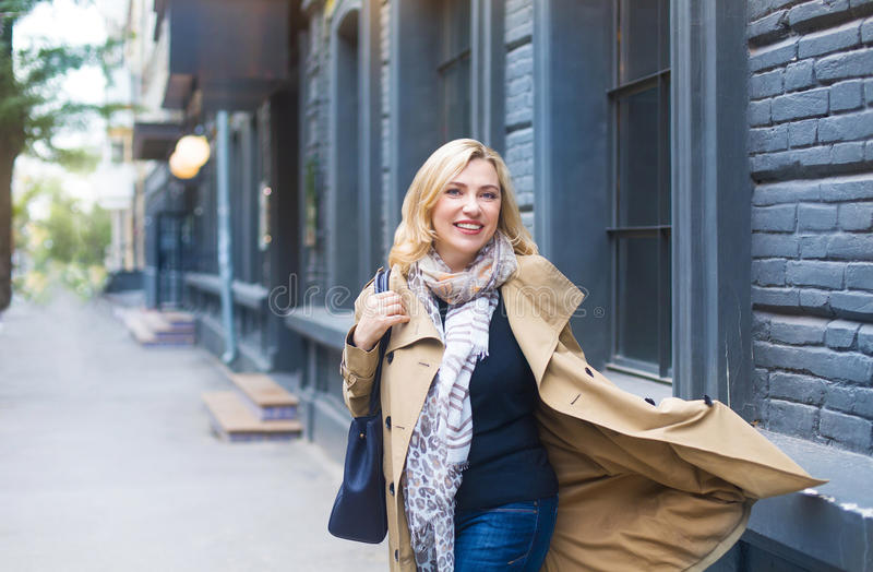 Middle age woman goes through the city and smiles. Happiness con stock image