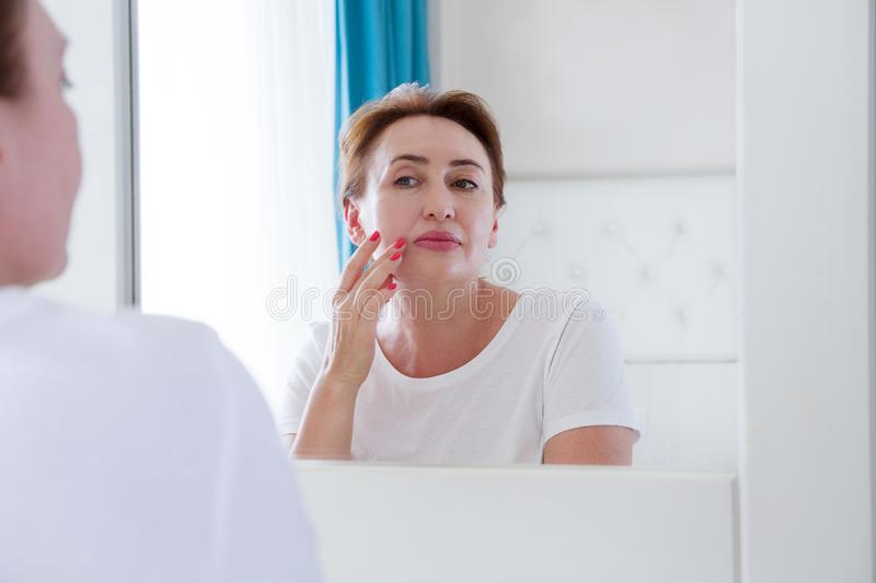 Middle age woman looking in mirror on face with pouches under the eyes . Wrinkles, anti aging skin care concept. Selective focus stock image