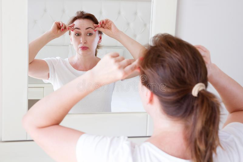 Middle age woman looking in mirror on face wrinkle forehead in bedroom. Wrinkles and anti aging skin care concept. Selective focus royalty free stock photo