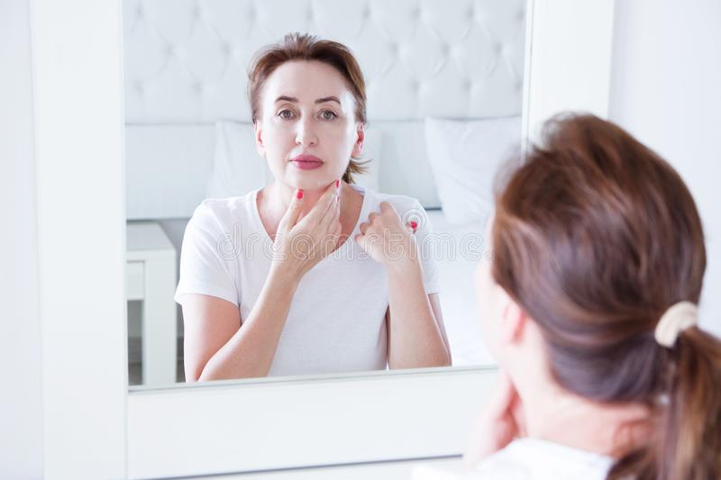 Middle age woman looking in mirror on face. Wrinkles and anti aging skin care concept. Selective focus.  stock photo