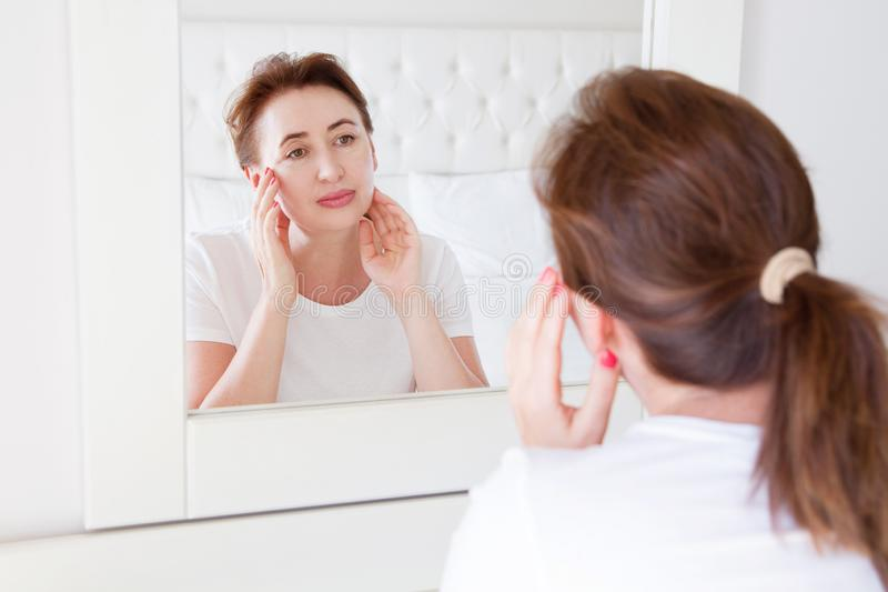 Middle age woman looking in mirror on face. Wrinkles and anti aging skin care concept. Selective focus royalty free stock image