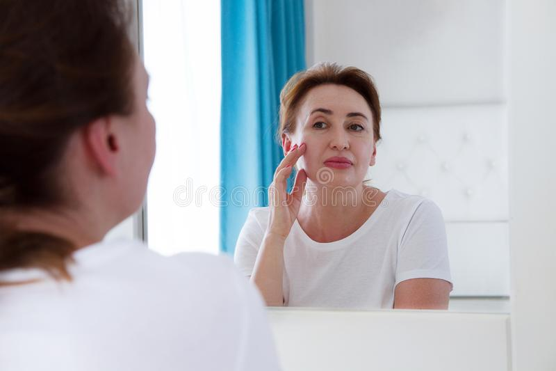 Middle age woman looking in mirror on face. Wrinkles and anti aging skin care concept. Selective focus.  royalty free stock photography
