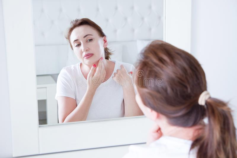 Middle age woman looking in mirror on face. Wrinkles and anti aging skin care concept. Selective focus.  stock photography