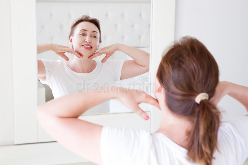 Middle age woman looking in mirror on face. Wrinkles and anti aging skin care concept. Selective focus royalty free stock images