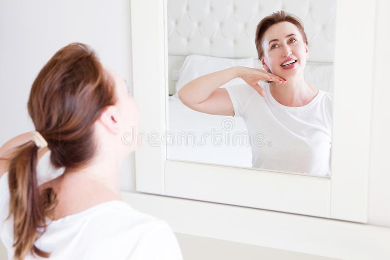 Middle age woman looking in mirror on face. Wrinkles and anti aging skin care concept. Selective focus.  royalty free stock photo