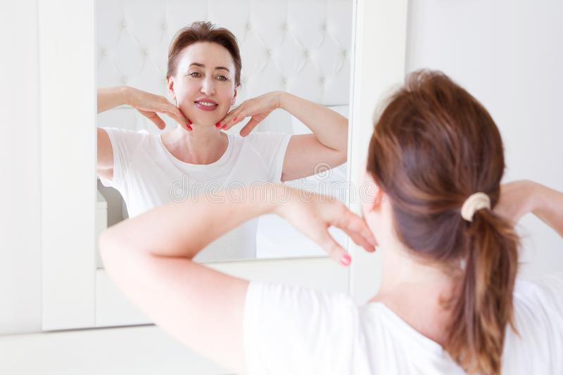 Middle age woman looking in mirror on face. Wrinkles and anti aging skin care concept. Selective focus.  royalty free stock image