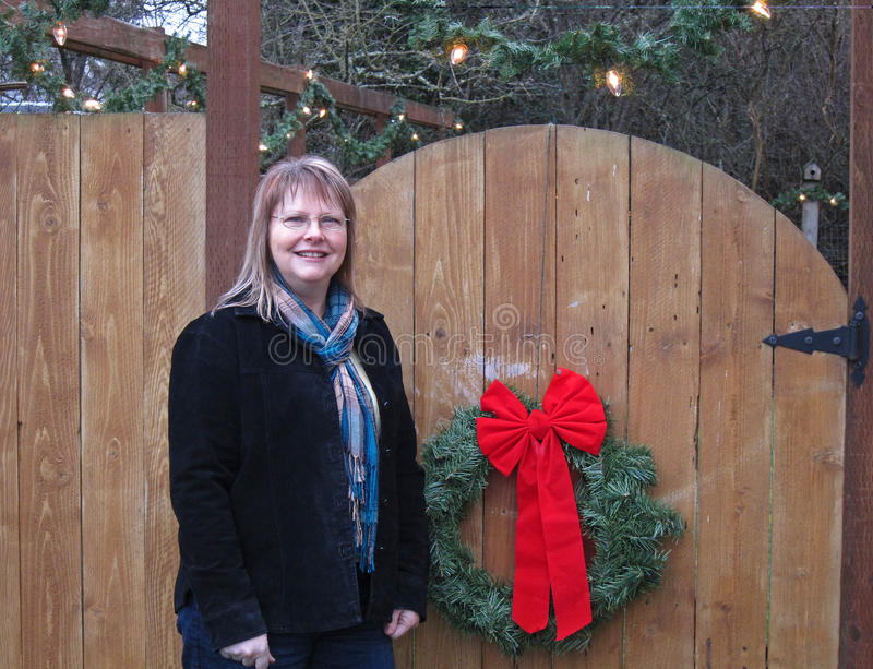 Middle Age Woman Portrait Near Christmas Wreath Fence. This is a portrait of a middle aged Caucasian woman near a wooden gate with a Christmas wreath on it royalty free stock image