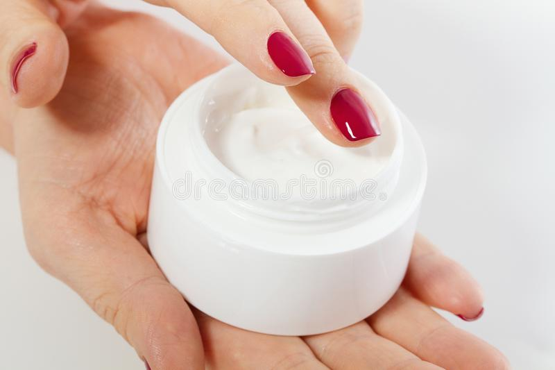 Middle age woman putting pomade on hand from the cream bottle isolated on white background. Spa and anti aging concept. royalty free stock image