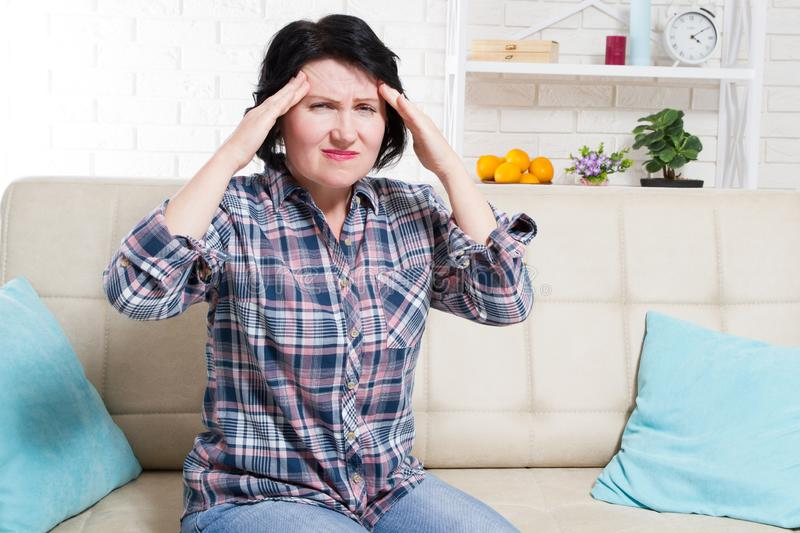 Middle age Woman suffering from a headache and stress holding her hands to her temples with her eyes opened in pain royalty free stock images
