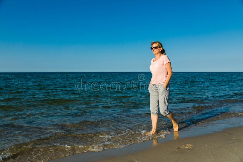 Woman waking on beach. Middle-age woman waking on beach stock image