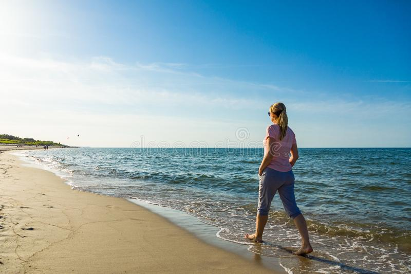 Woman waking on beach. Middle-age woman waking on beach stock photography