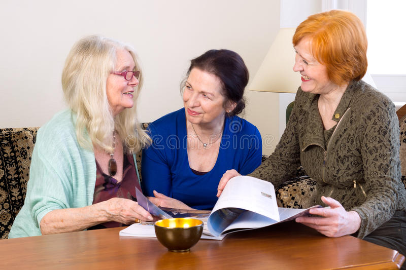 Middle Age Women Friends Talking at Living Area. Three Middle Age Women Best Friends Enjoying their Talks at the Living Area While Scanning a Magazine stock photos