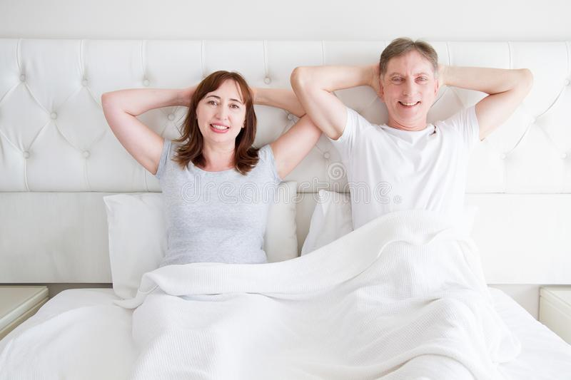 Middle age woman and man in bed. Senior couple dreaming and thinking in bedroom. Template and blank t shirt. Copy space. Mock up stock photo