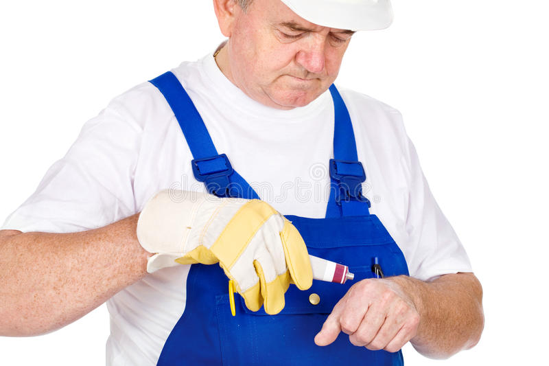 Middle age worker putting cream on his wound