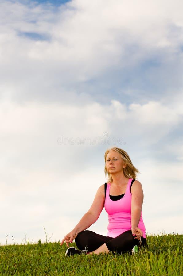 Middle-aged женщина в ее 40s meditating стоковое фото rf