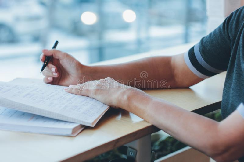 Middle-aged adult woman doing homework on the Chinese language i royalty free stock images