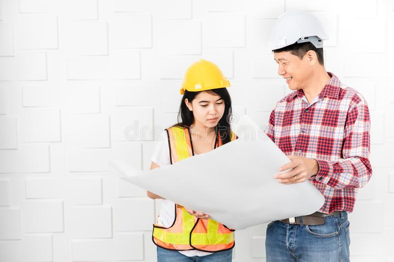 Asian architect at construction site office. Middle aged Asian architect, in jeans and checked shirt, wearing hardhat, teaching his young female Asian assistant royalty free stock photos
