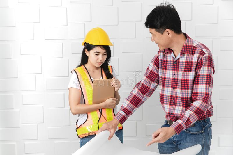 Asian architect at construction site office. Middle aged Asian architect, in jeans and checked shirt, wearing hardhat, teaching his young female Asian assistant stock images