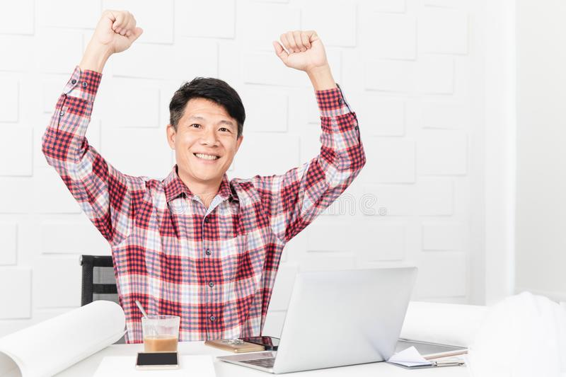 Asian architect at construction site office. Middle aged Asian handsome architect, in checked shirt, working at construction site office, making winner gesture stock photo